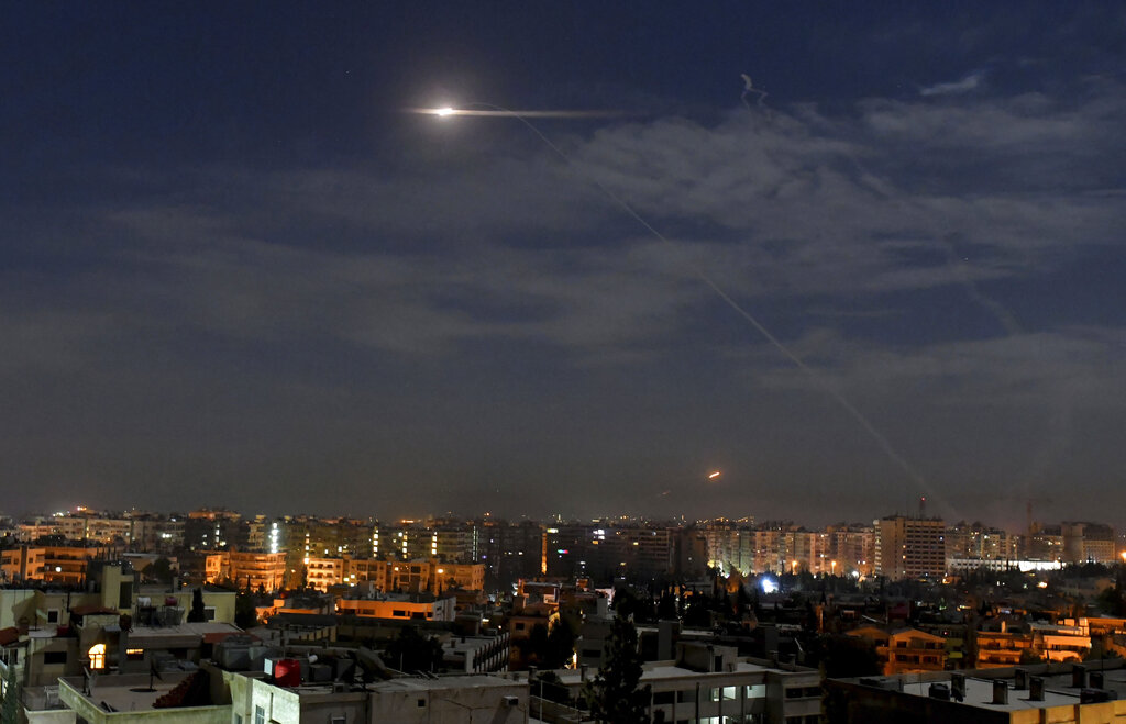 In this photo released by the Syrian official news agency SANA, missiles fly into the sky near the international airport in Damascus, Syria, on Monday.
