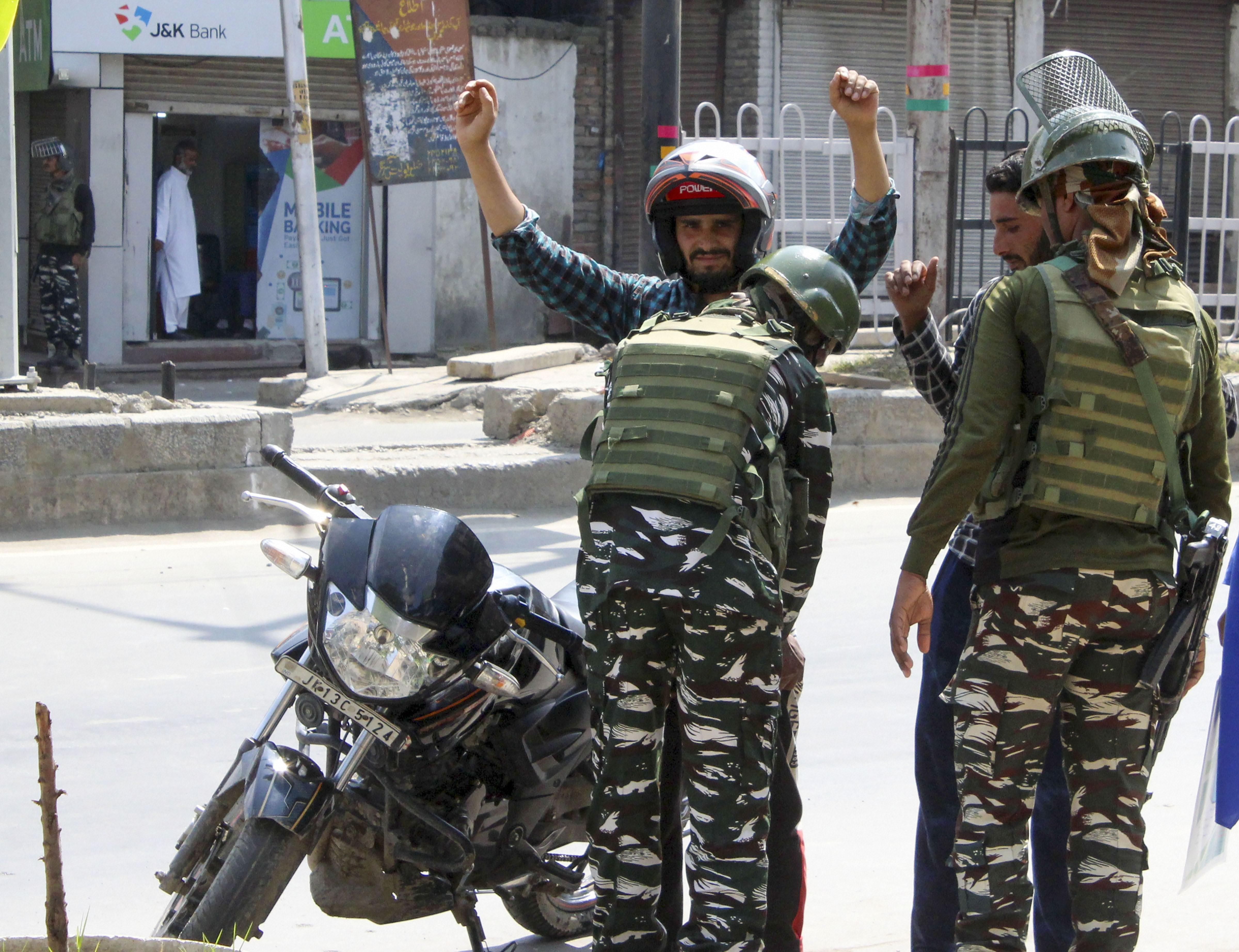 Security personnel frisk a biker in Srinagar on September 1.