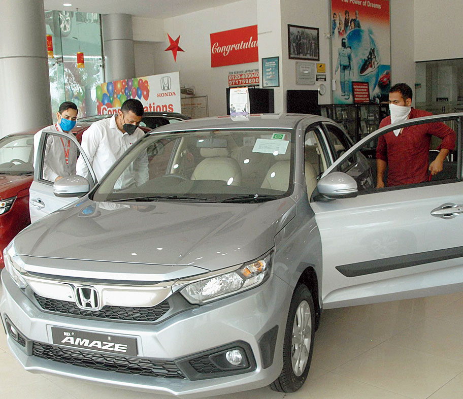 Customers check out cars at a showroom in Noida on Wednesday.