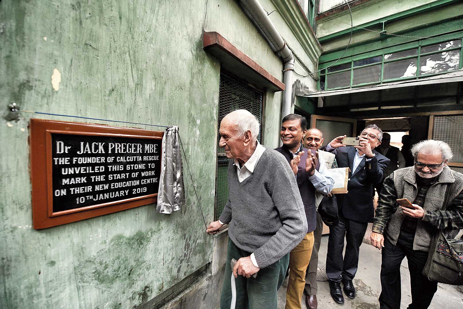 Jack Preger unveils the plaque of Calcutta Rescue's new education centre on Thursday.