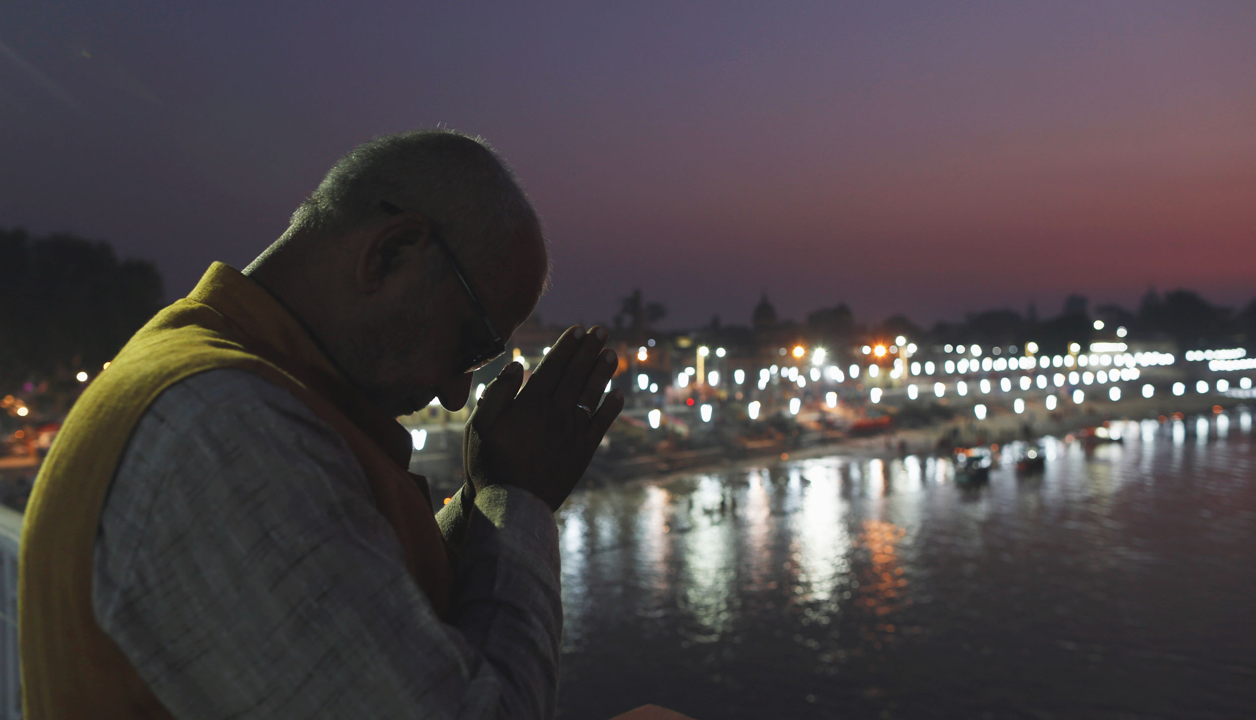 A Hindu devotee prays on the banks of Saryu River after the sunset in Ayodhya on November 10, 2019.