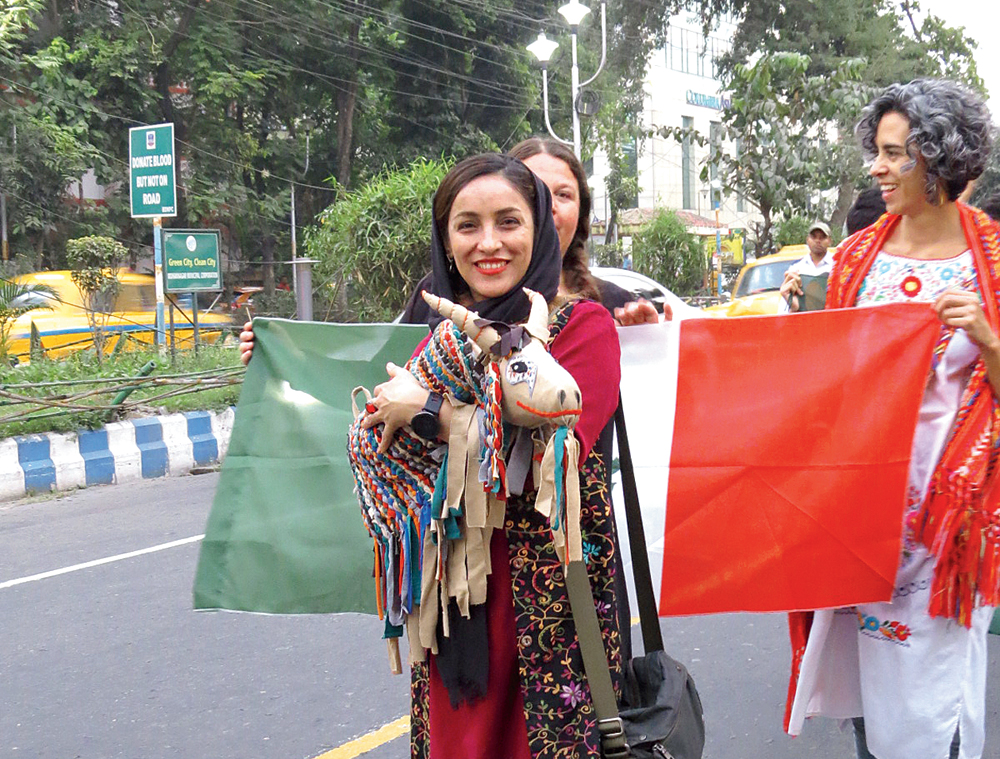 A participant from Iran takes part in the procession with a puppet