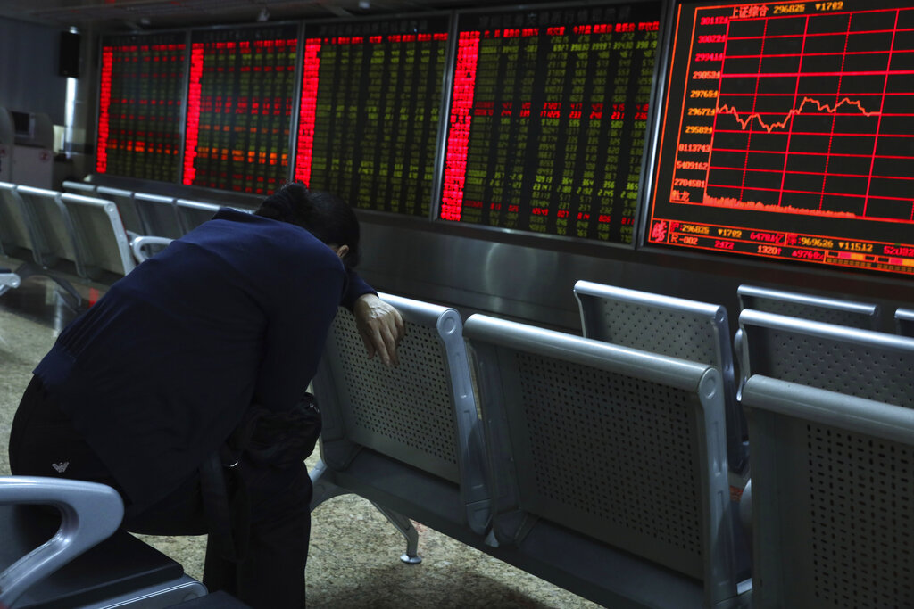 An investor rests while monitoring stock prices at a brokerage in Beijing on September 25, 2019.