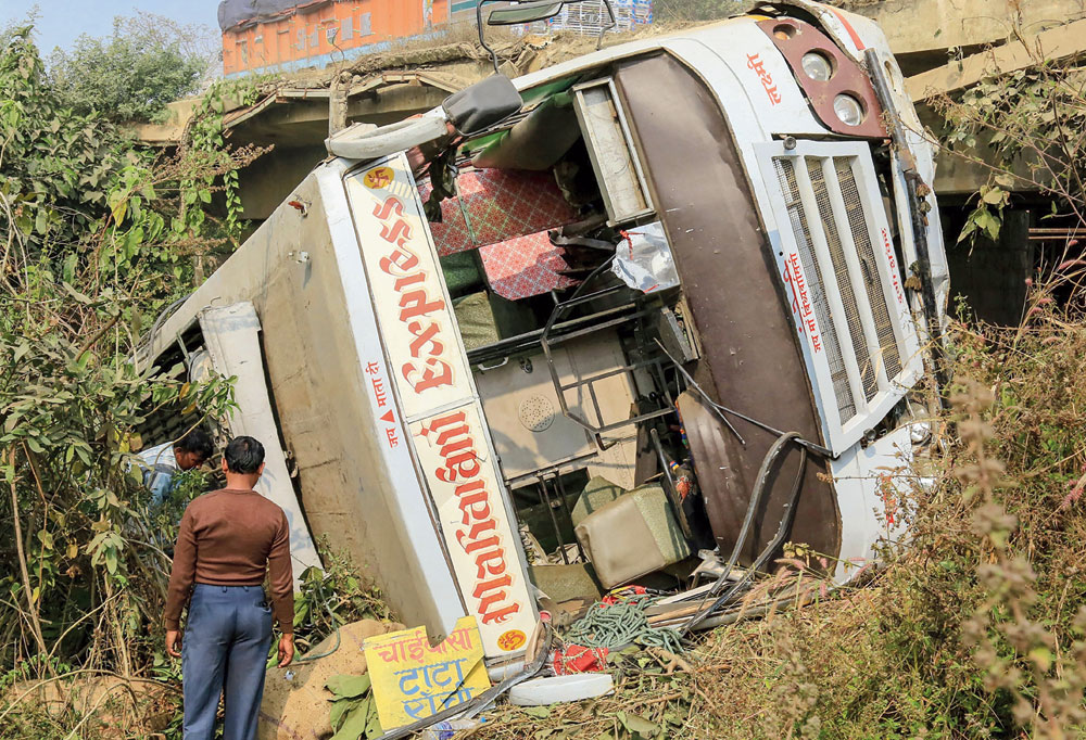 Dangerous driving: The bus that fell off the under-construction bridge at Shankardiha on NH-33 in Seraikela-Kharsawan on Monday.