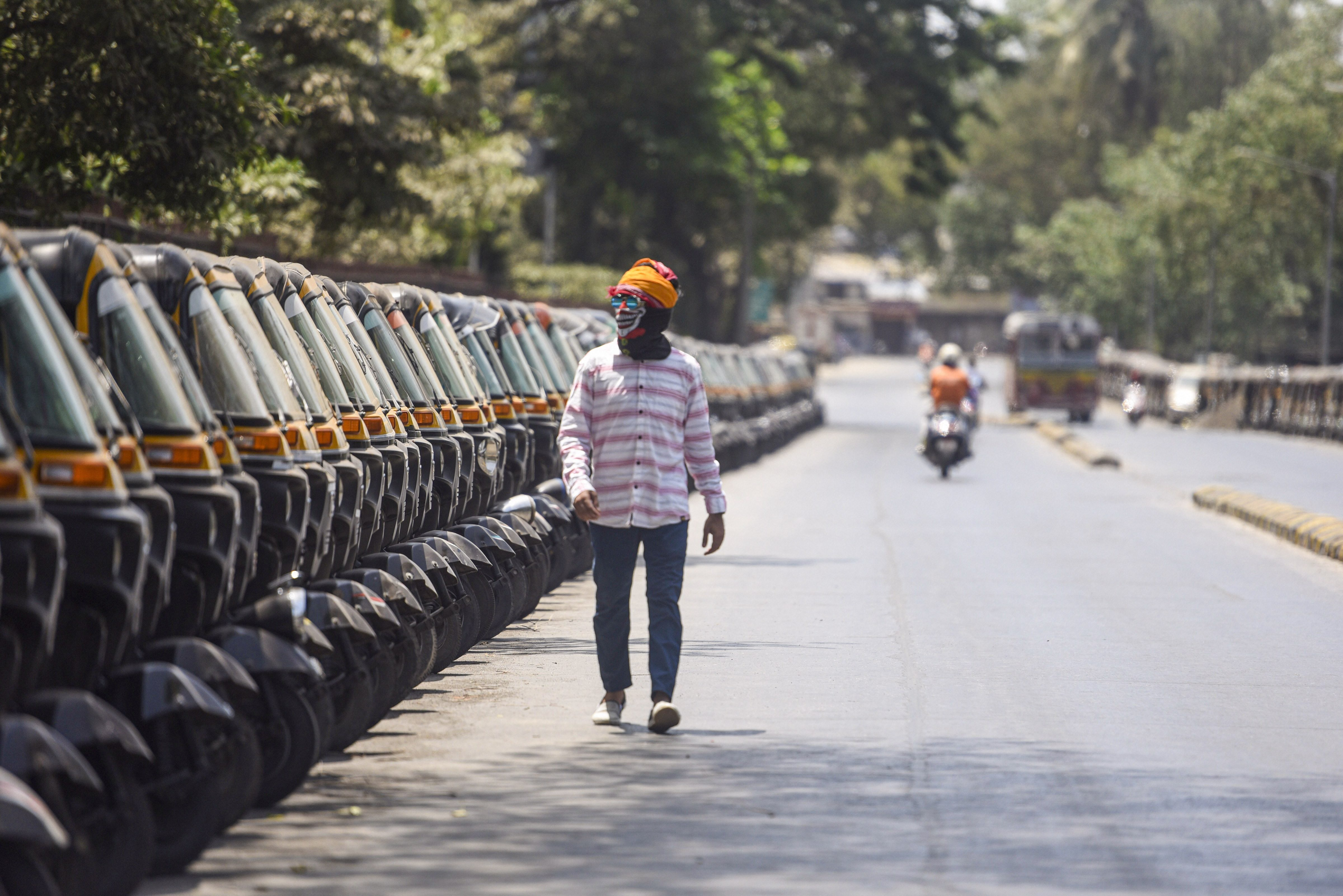 A pedestrian wearing a mask walks past parked auto rickshaws during the nationwide lockdown at Kandivali in Mumbai on Friday.
