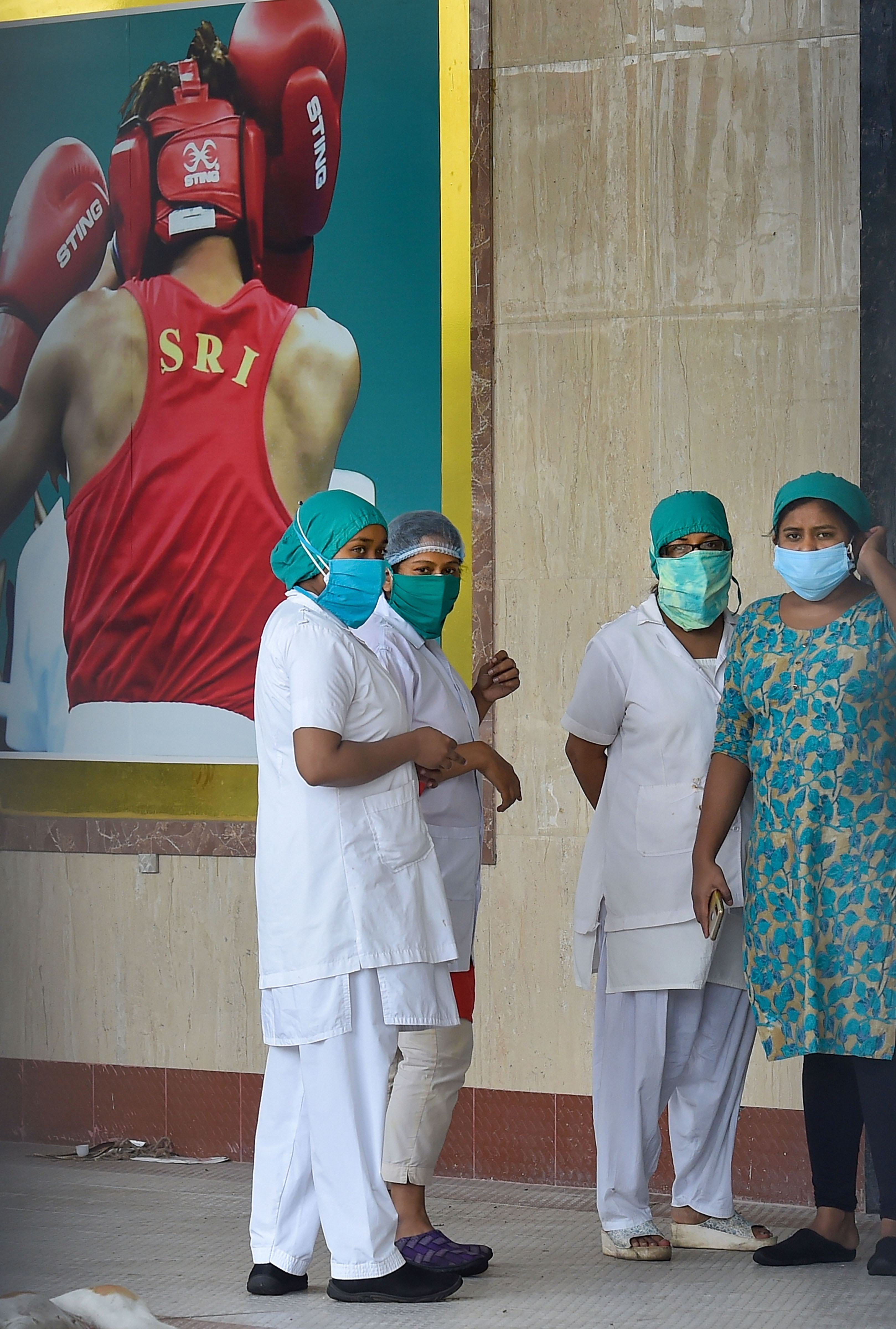 Health workers stand outside a quarantine facility at Dumerjola stadium in Calcutta on Thursday.