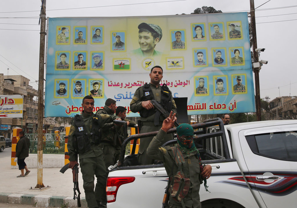 In this March 28, 2018 file photo, members of the Kurdish internal security forces stand on their vehicle in front of a giant poster showing portraits of those killed fighting against the Islamic State group, in Manbij, north Syria.