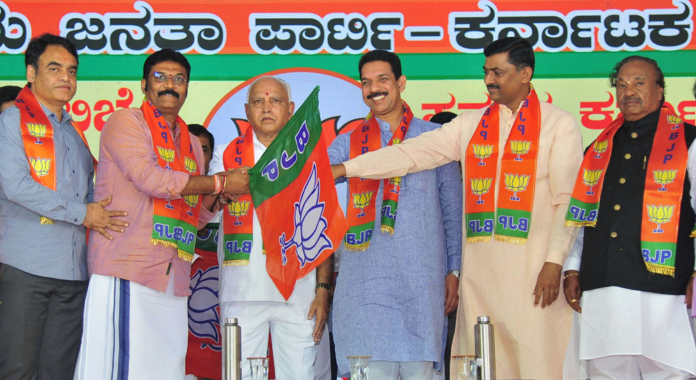 Chief Minister B.S. Yediyurappa, BJP State Unit President Nalin Kumar Kateel and BJP National general secretary Muralidhar Rao hand over the party flag to MLA Anand Singh during a programme to induct the disqualified MLAs, in Bangalore, Thursday, November 14, 2019.