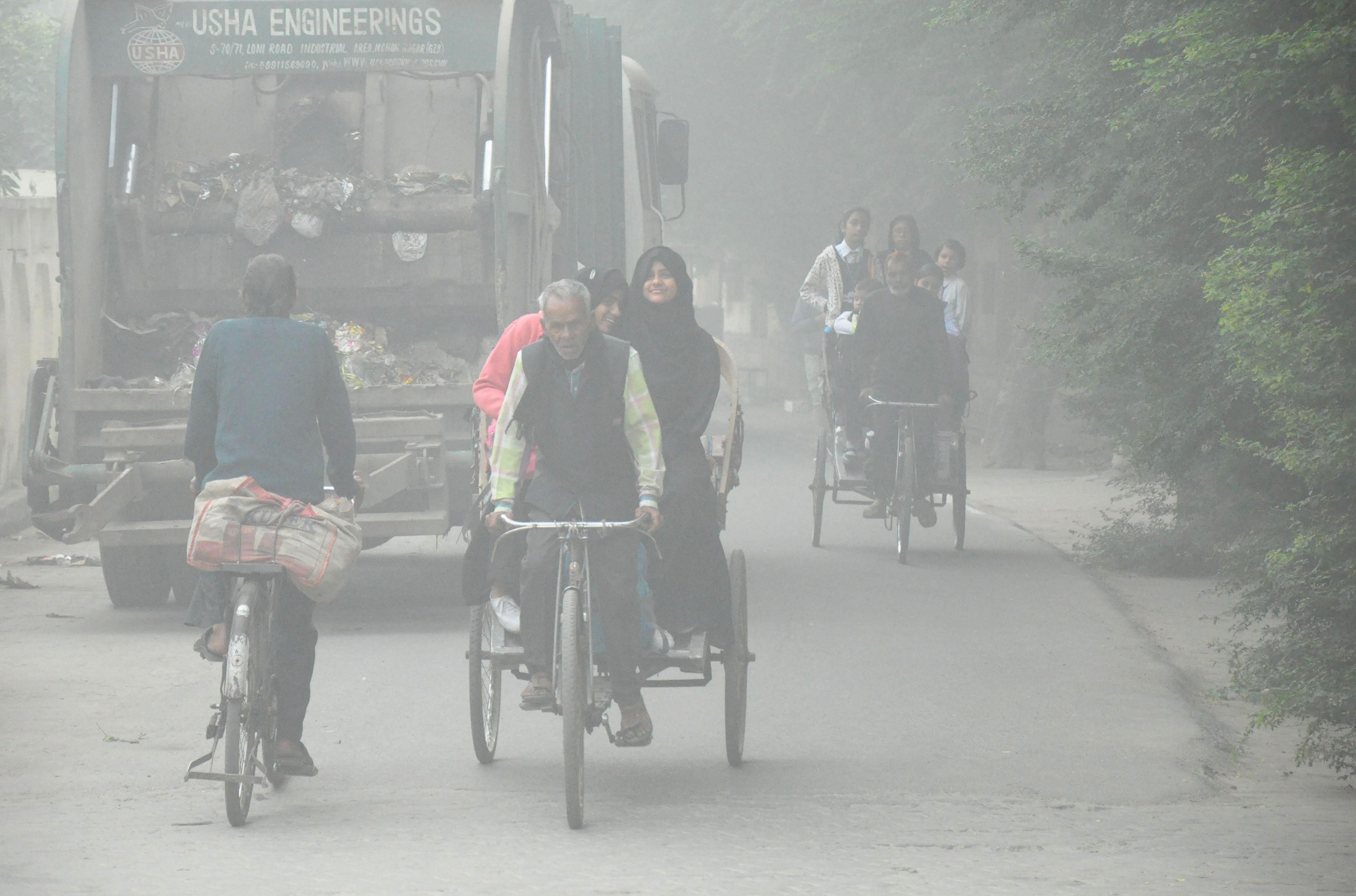 Rickshaw pullers ride through dense smog, in Moradabad, Monday, November 4, 2019.