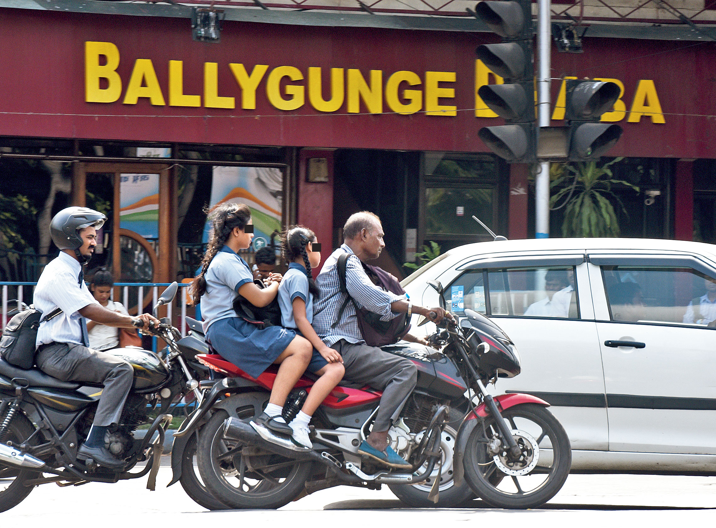 A man rides past Ballygunge Dhaba with two girls in school uniform on the pillion. None was wearing a helmet.
