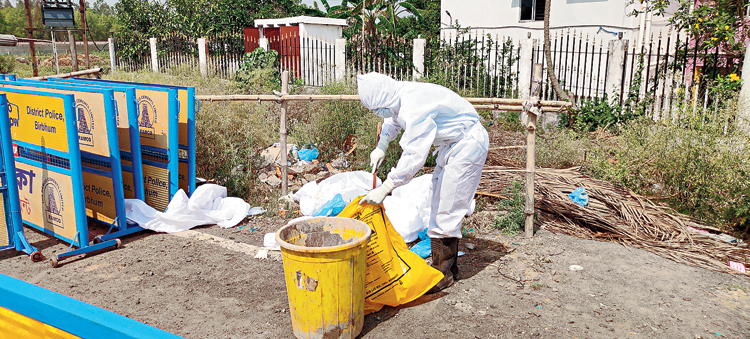 A health worker picks the PPEs dumped on the road near the quarantine centre on Sunday.