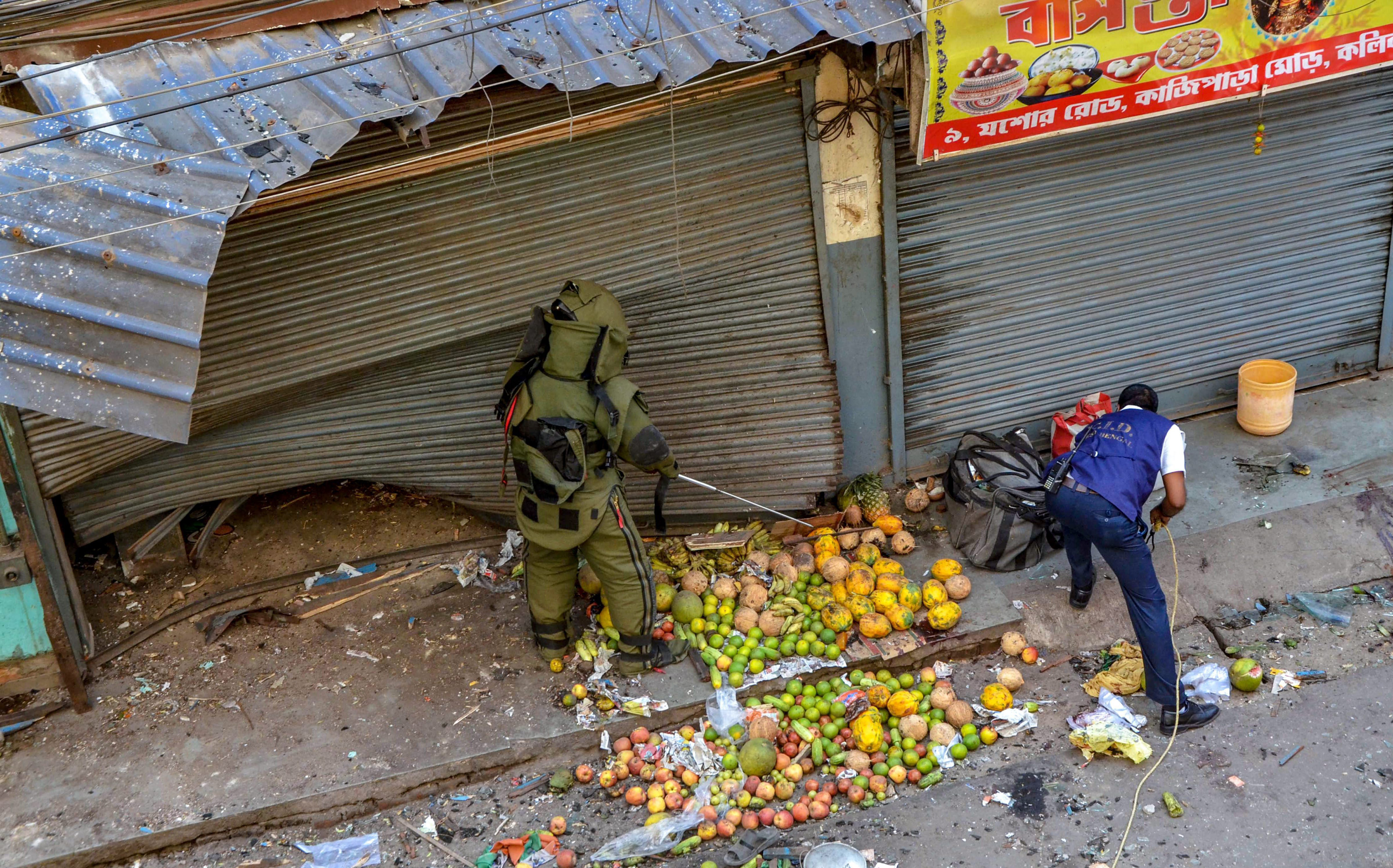 A bomb disposal squad member inspects the site of low intensity bomb blast at Kazipara, Nagerbazar area of Dumdum, in Kolkata on Tuesday.