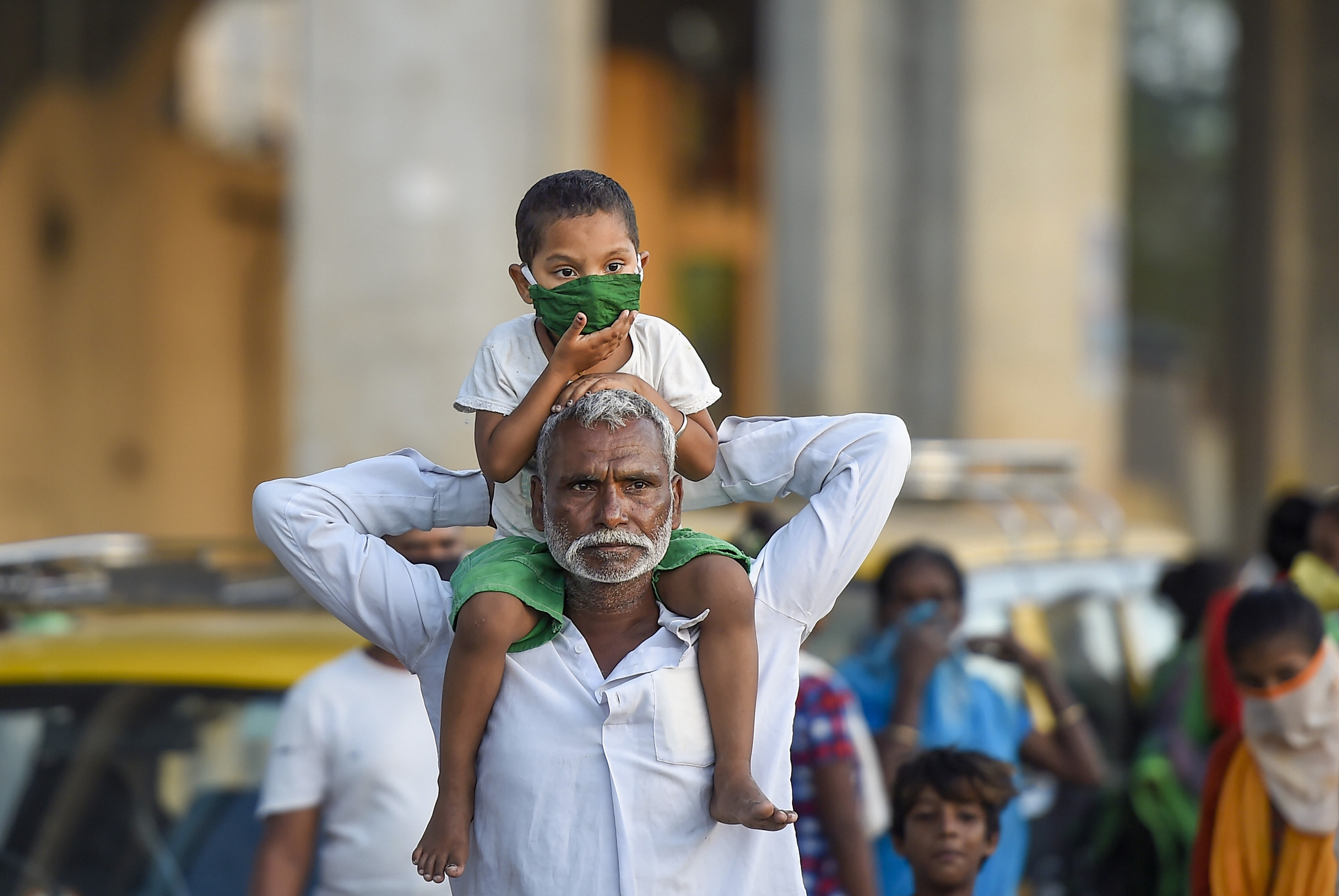 A child wearing a face mask sits on the shoulder of an elderly man during the nationwide lockdown, imposed in the wake of the coronavirus pandemic, at Sion in Mumbai, Wednesday, April 8, 2020.
