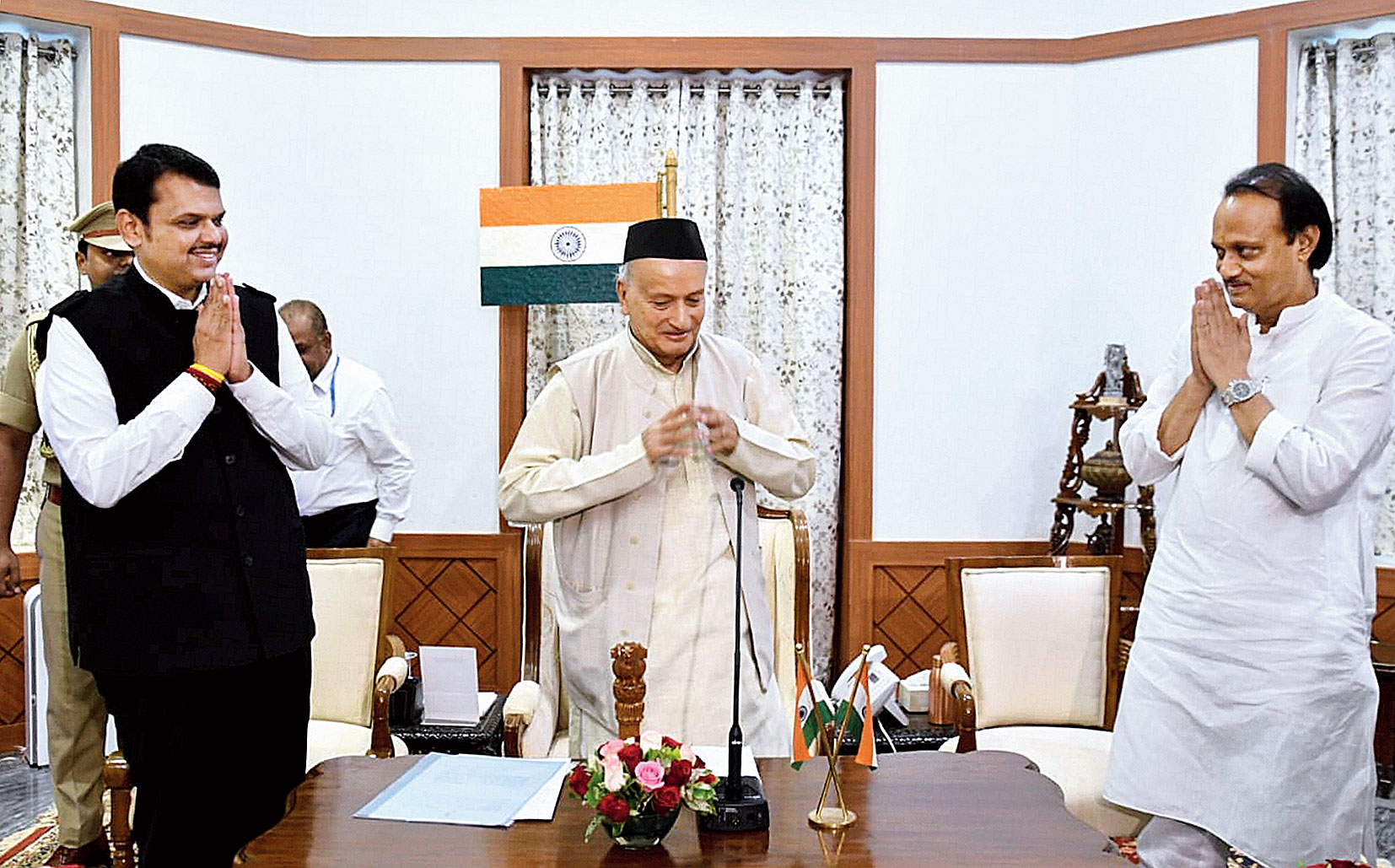 Maharashtra governor Bhagat Singh Koshyari flanked by newly appointed chief minister Devendra Fadnavis and deputy chief minister Ajit Pawar (right) after the oath-taking ceremony at 7.50am in Mumbai on Saturday.