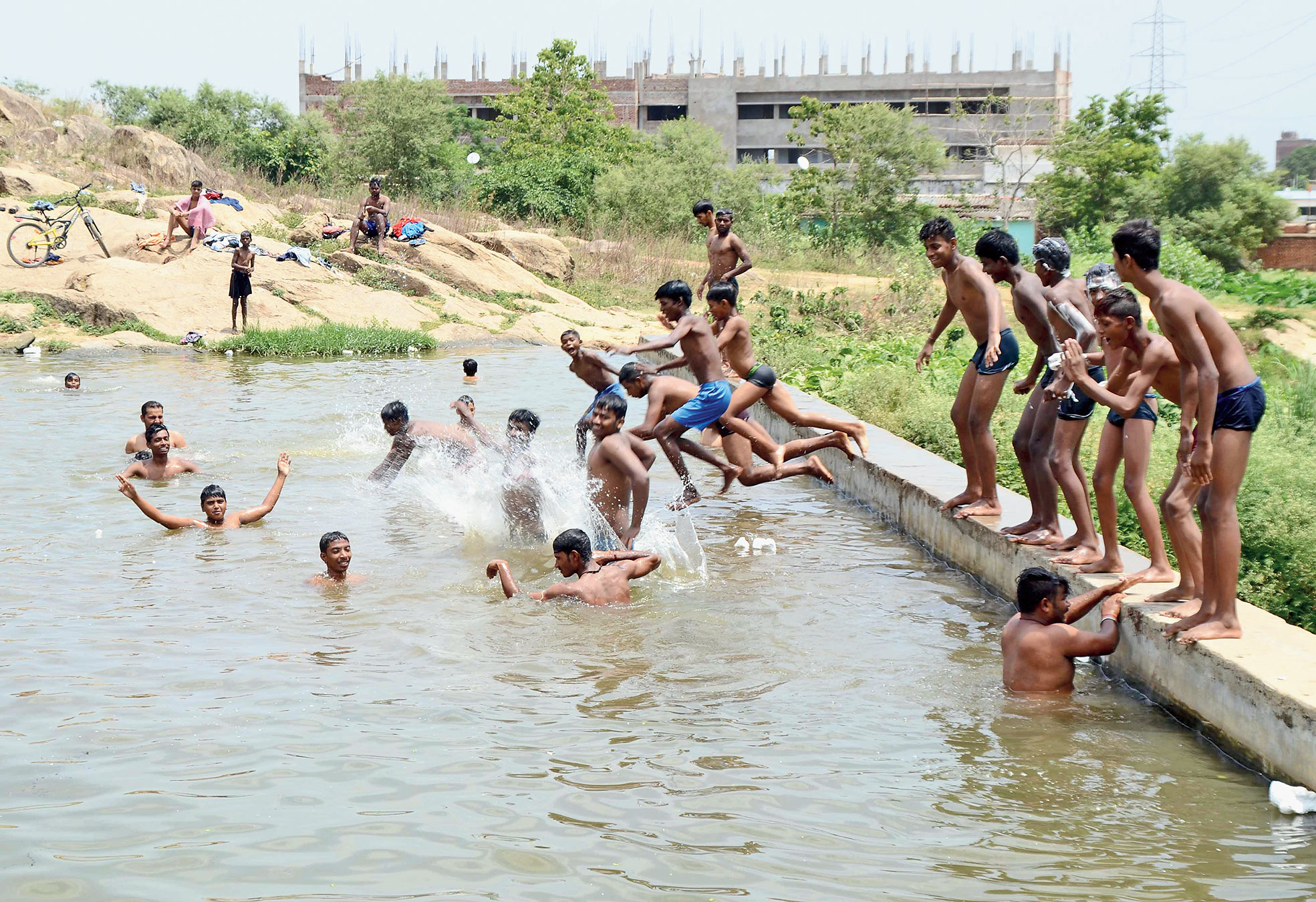 Boys enjoy a splash at PHD Colony pond in Ranchi on Thursday.