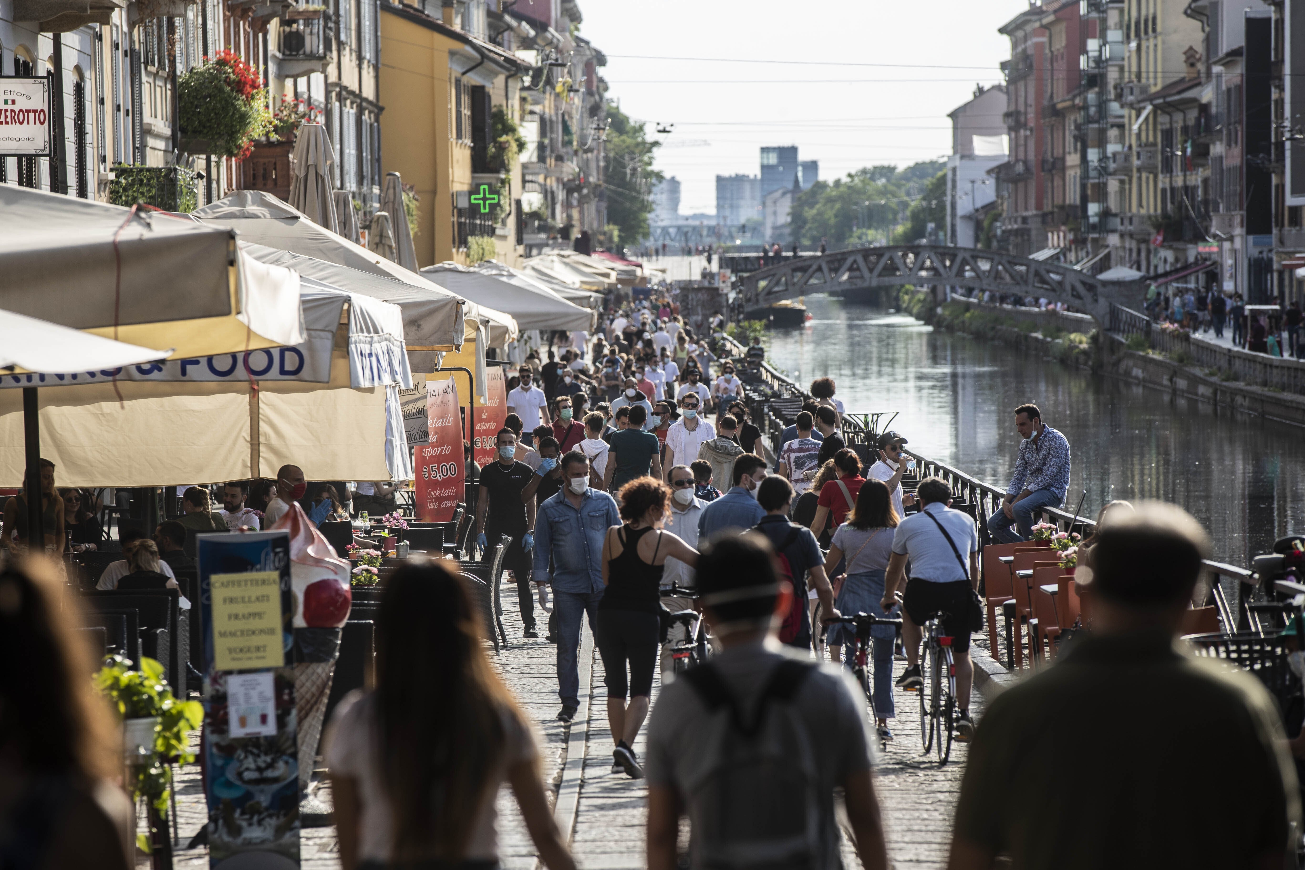 People take a walk and relax at the Naviglio Grande canal, in Milan, Italy