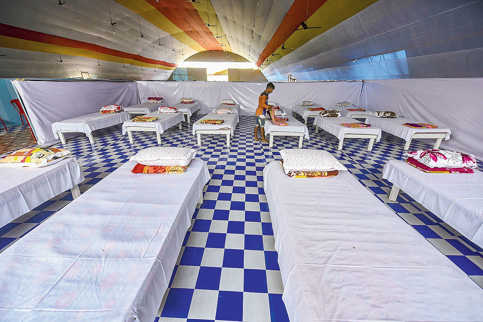 A worker prepares beds at the quarantine centre at Sarusajai stadium in Guwahati on April 15.