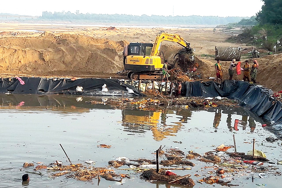 A crane lifts waste from an artificial immersion pond near Kuakhai river in Bhubaneswar.