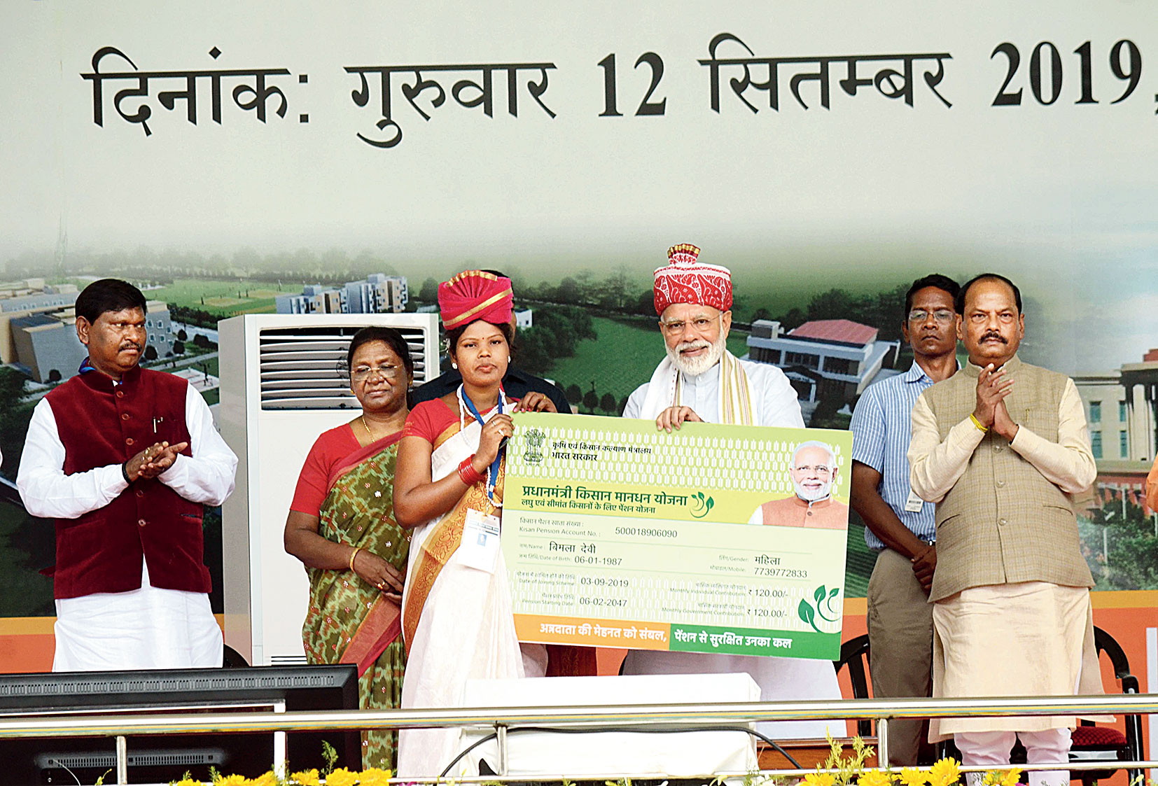 Prime Minister Narendra Modi hands over a symbolic pension card to Bimla Devi, a farmer from the state, at Prabhat Tara ground in Ranchi on Thursday as chief minister Raghubar Das and governor Droupadi Murmu applaud.