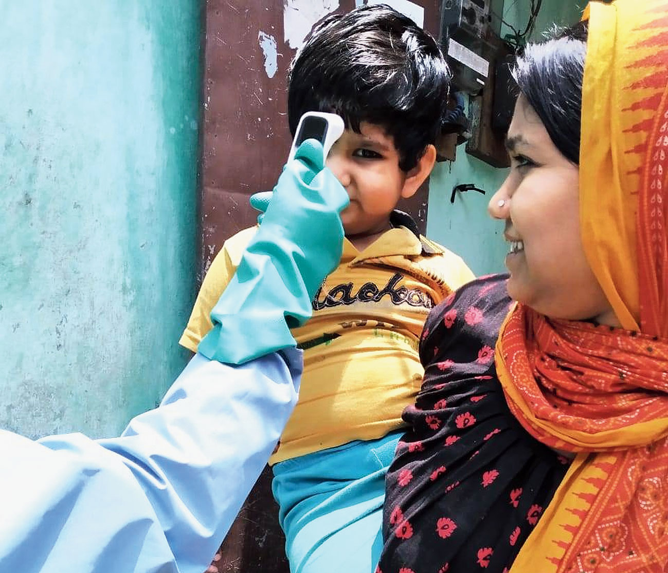 A health worker checks temperature of a child who is in home quarantine at a village in Cooch Behar