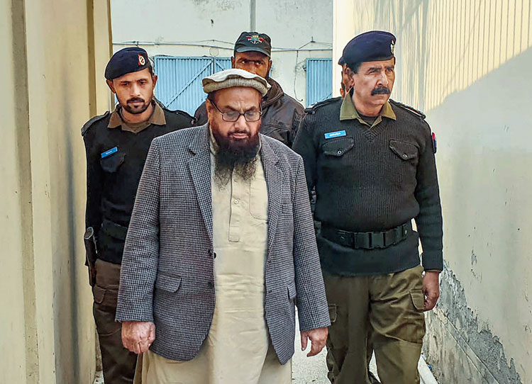 A picture taken on December 20 shows Hafiz Saeed (centre) entering an anti-terrorism court in Lahore.