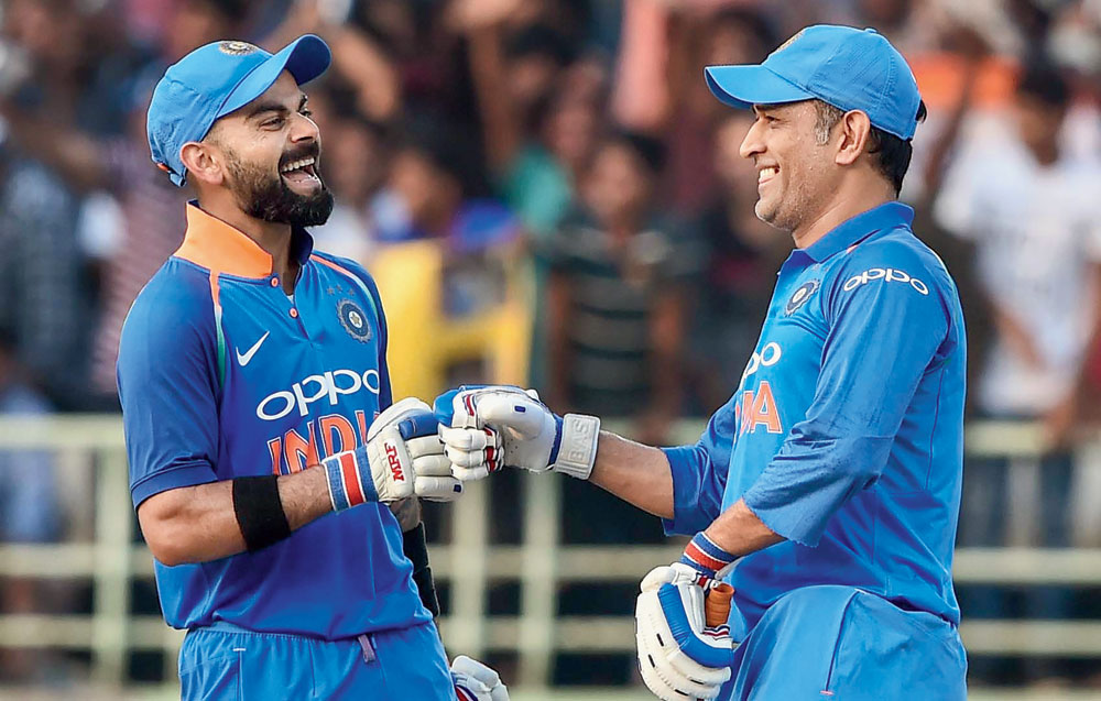 Welcome to the club: Mahendra Singh Dhoni congratulates Virat Kohli after the Indian captain completed 10,000 ODI runs on Wednesday.