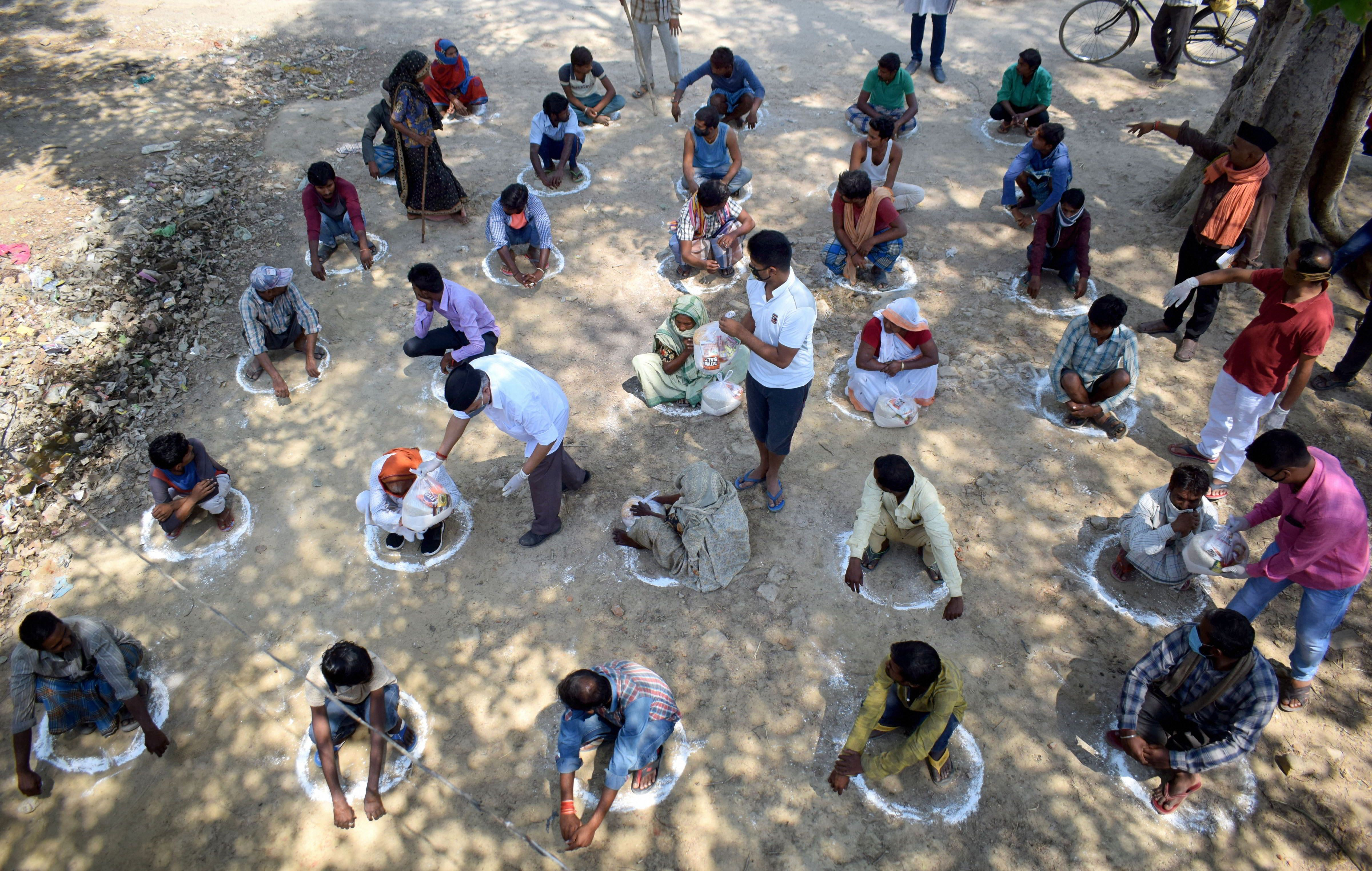Seva Bharati volunteers distribute groceries among needy people sitting in painted circles to maintain social distancing during a nationwide lockdown in the wake of coronavirus pandemic, at a village in Prayagraj, Wednesday, April 22, 2020.