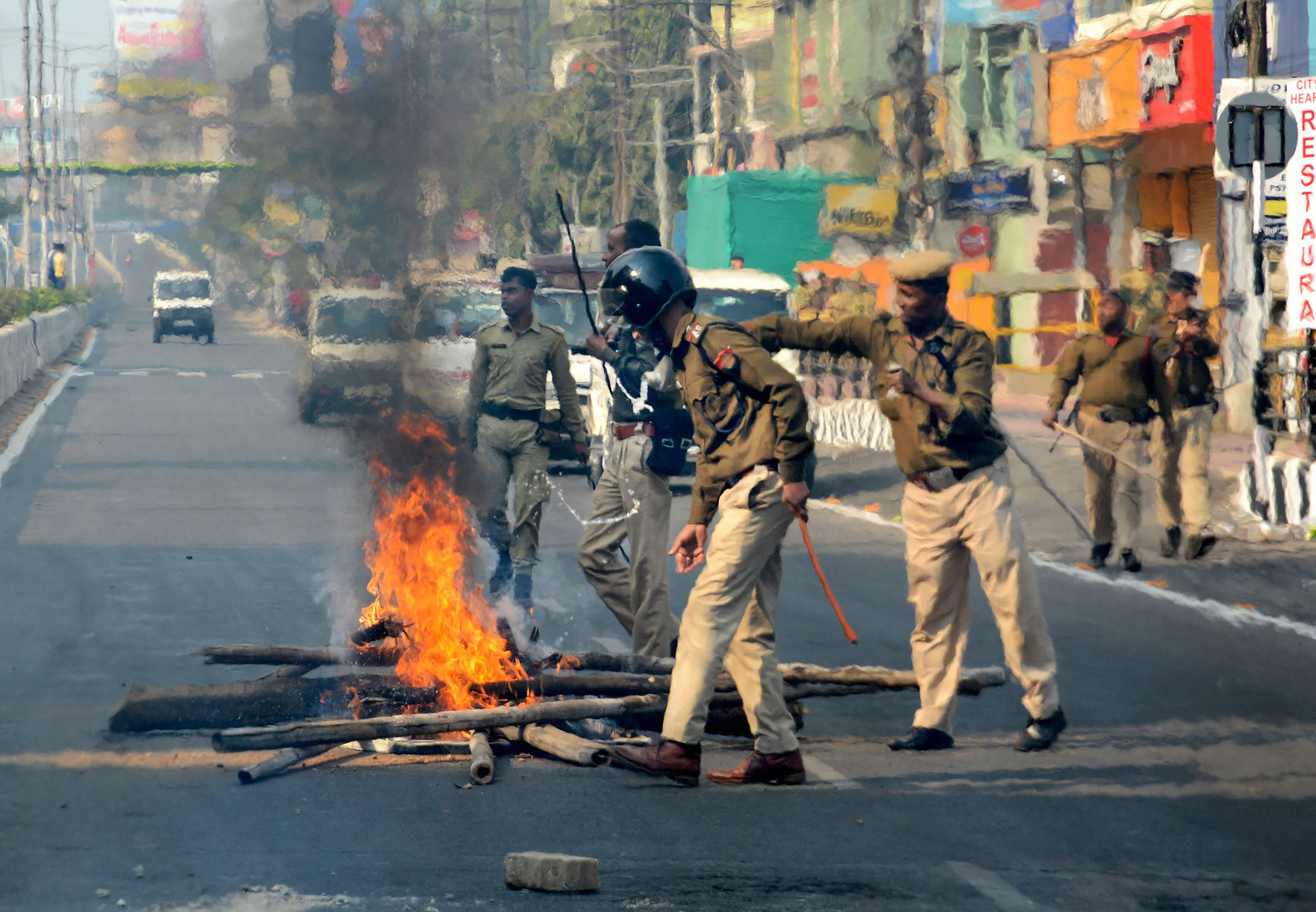 Security personnel remove burning logs that were set on fire by the protesters to block a road, during an agitation against the Citizenship (Amendment) Bill, in Guwahati, Thursday, December 12, 2019.
