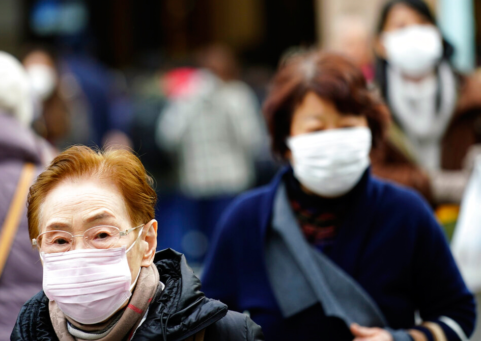 Pedestrians wear protective masks as they walk through a shopping district in Tokyo Thursday, January 16, 2020. Japan's govt said a man treated for pneumonia after returning from China has tested positive for the new coronavirus identified as a possible cause of an outbreak in China.