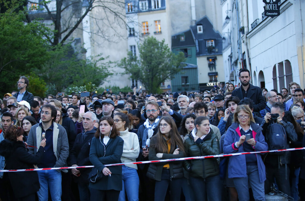 People watched as flames and smoke rose from Notre Dame cathedral as it burnt in Paris on April 15.
