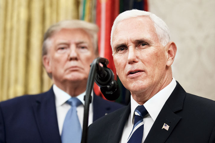 Vice-President Mike Pence (right) speaks at the White House as US President Donald Trump looks on.