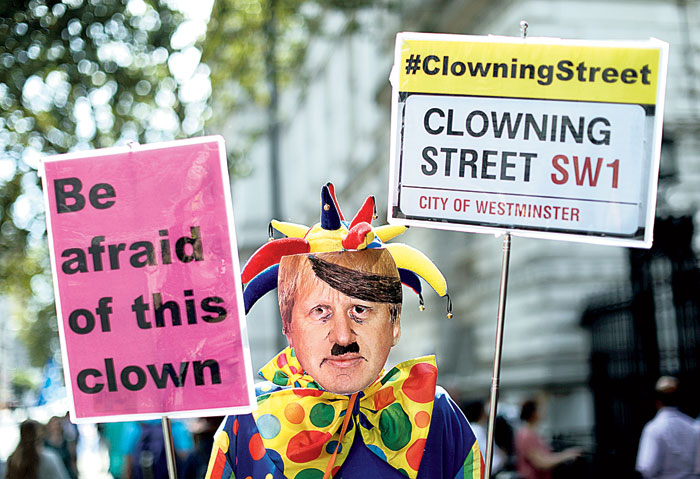 A man dressed as a clown and wearing a Boris Johnson mask  protests near the Downing Street gate on Thursday