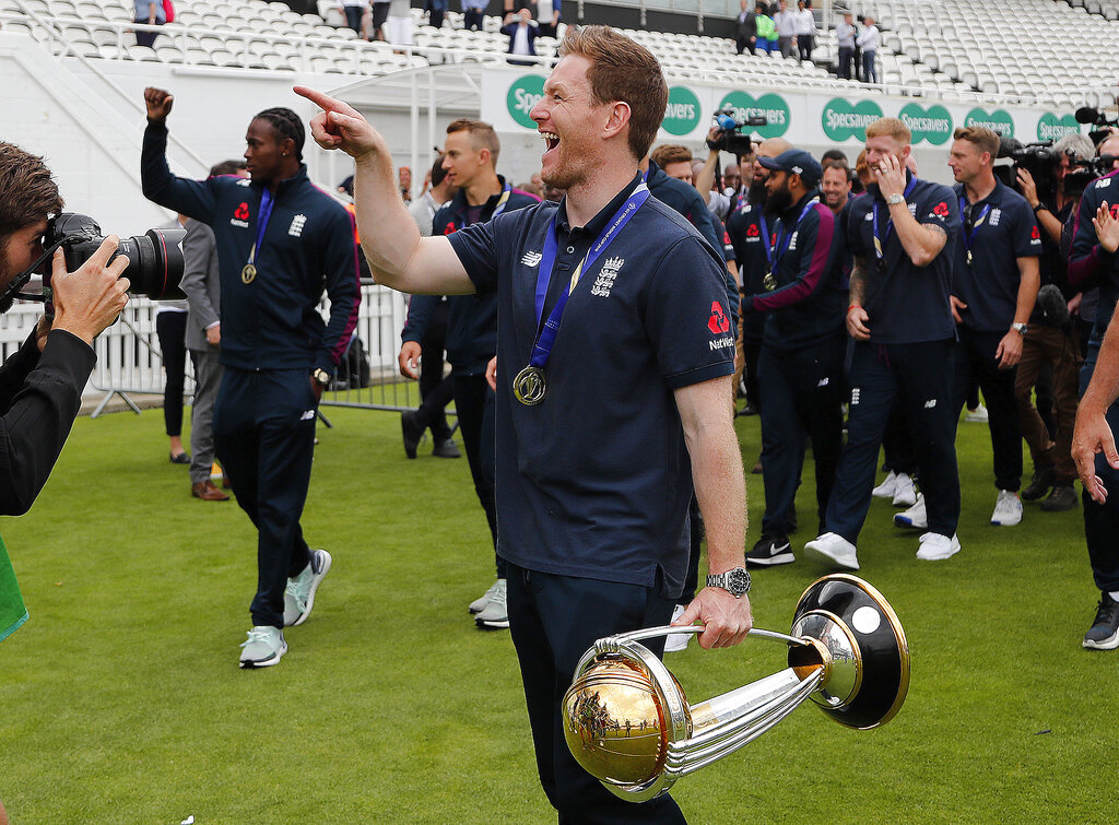England's Eoin Morgan, centre, and teammates celebrate with the trophy at the Oval in London, on Monday, July 15, 2019