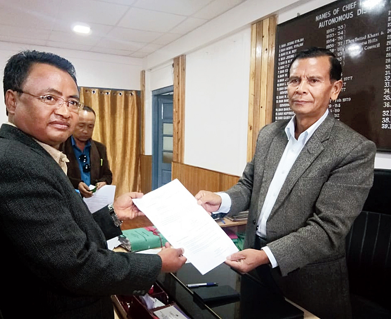 KHADC chief H.S. Shylla receives a copy of the report on the lineage act from consultative committee chairman Mansturdy Nongrem in Shillong on Tuesday.