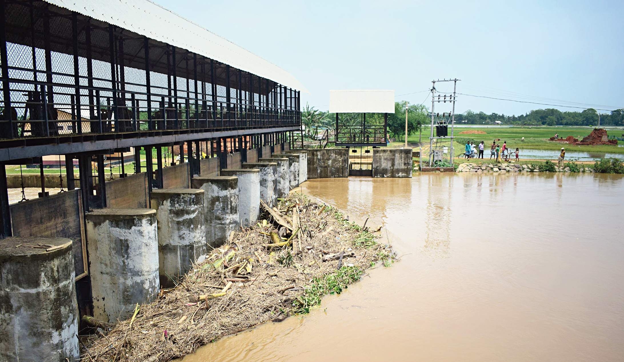 Debris piles up at a switch gate on the Singra river at Boko in Kamrup district on Sunday.
