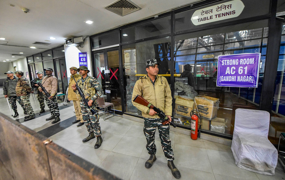 Security personnel stand guard outside a strong room, a day after national capital went to polls for the Assembly election, at a counting centre in Akshardham, New Delhi