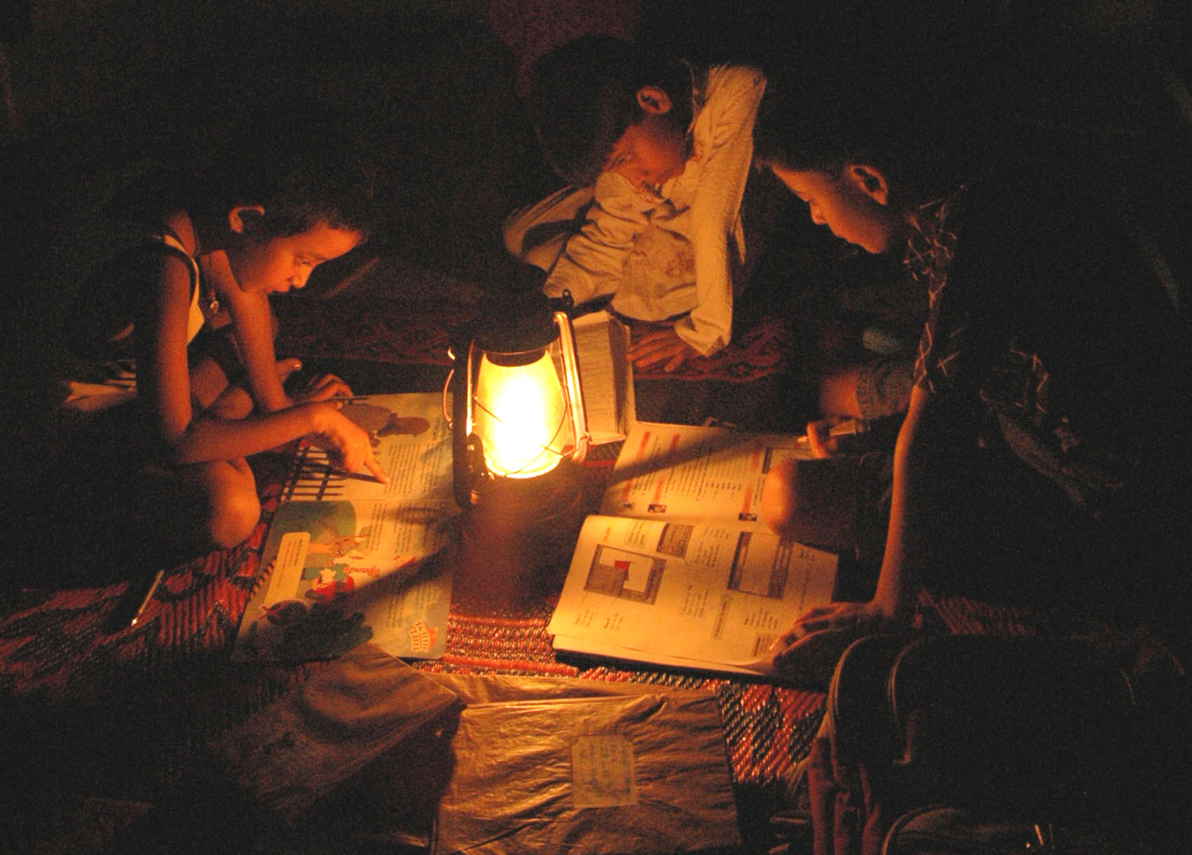 Children study under the light of a lantern at Hirapur in Dhanbad on Saturday evening during a power cut.