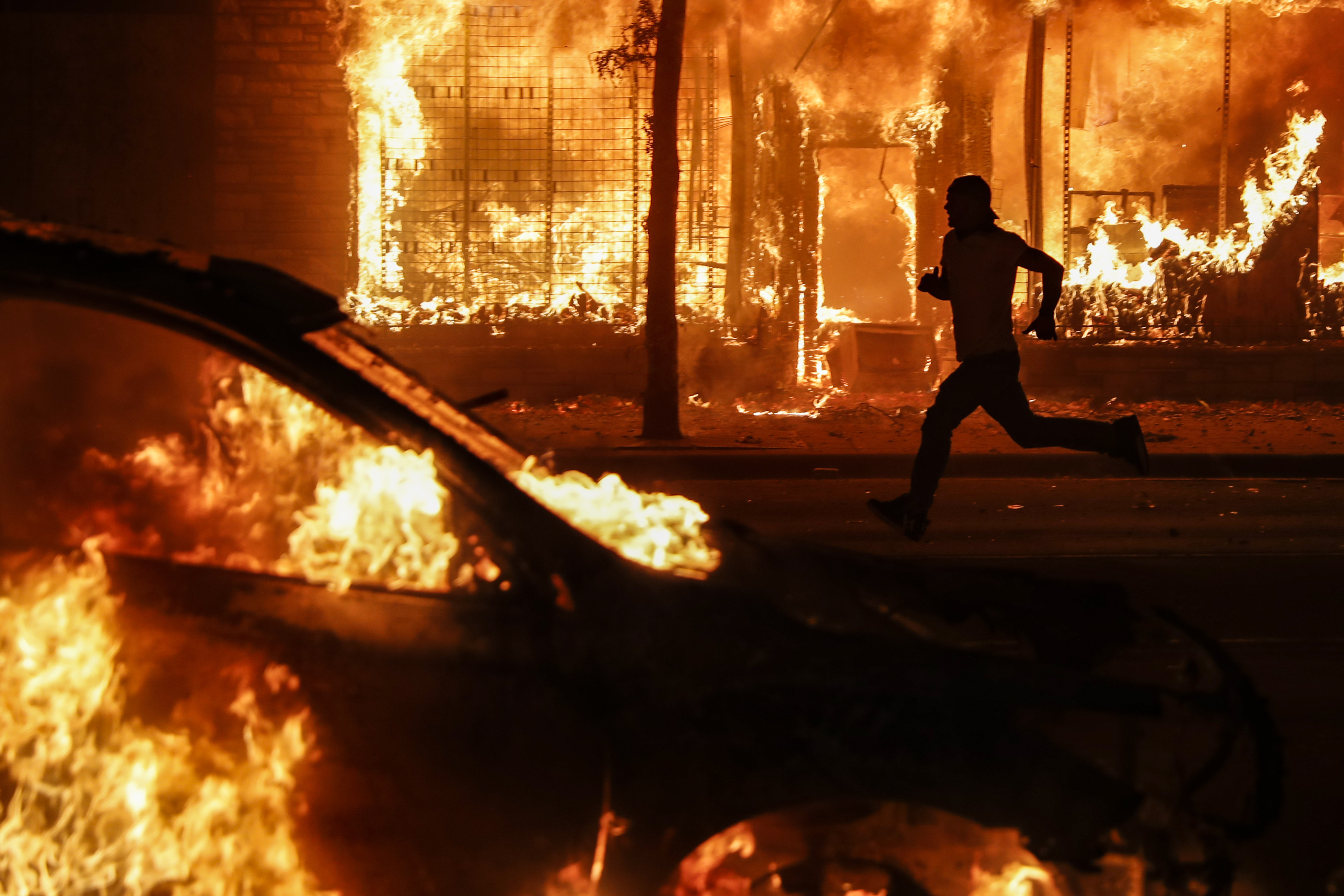 A protester runs past burning cars and buildings on Chicago Avenue