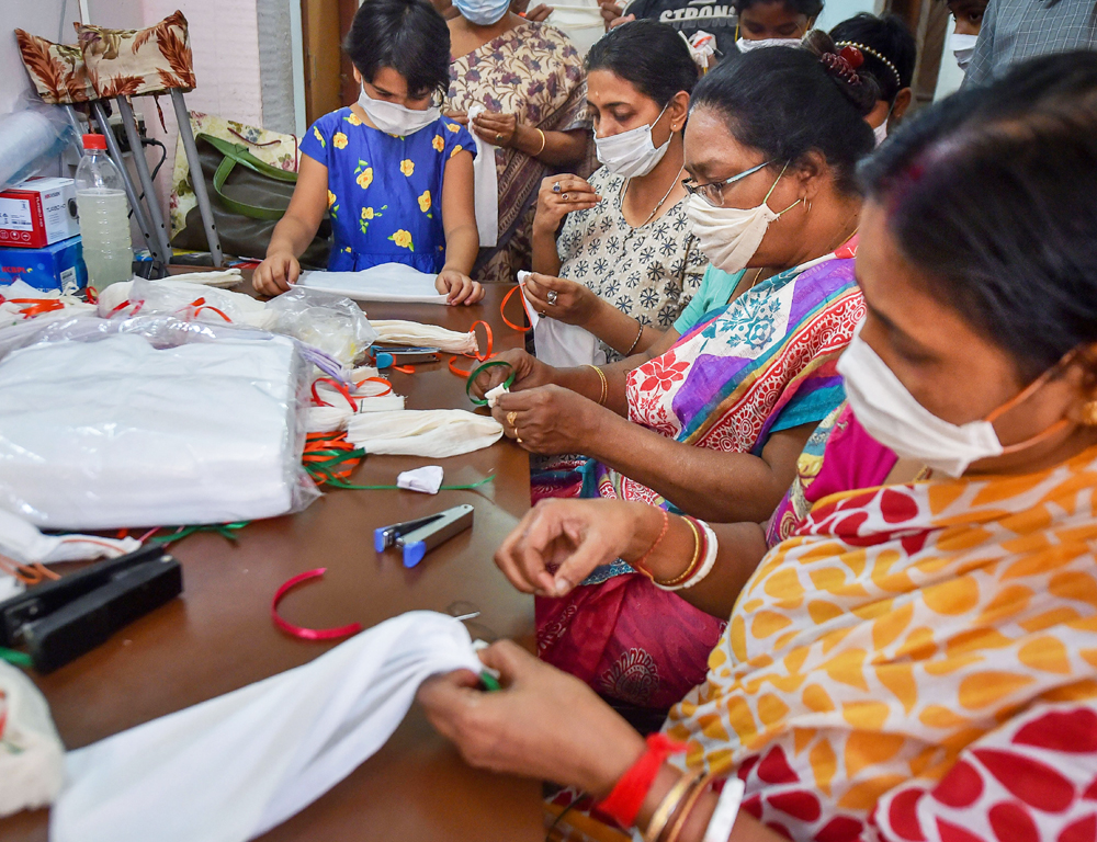 Women and children prepare masks to be distributed for free in the wake of coronavirus pandemic in Calcutta, Thursday, March 19, 2020.