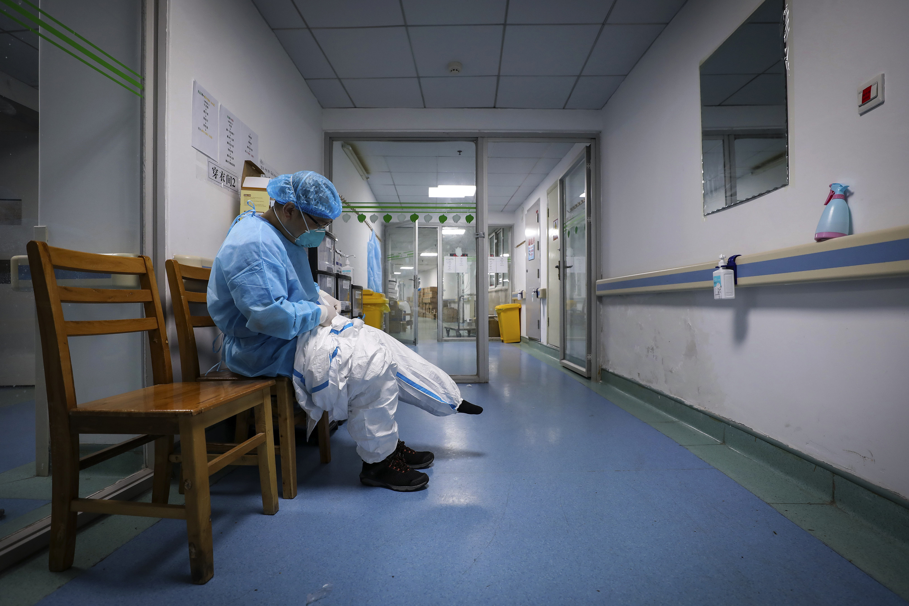 A doctor puts on a protective suit as he prepares to check on the patients at Jinyintan Hospital designated for coronavirus infected patients, in Wuhan