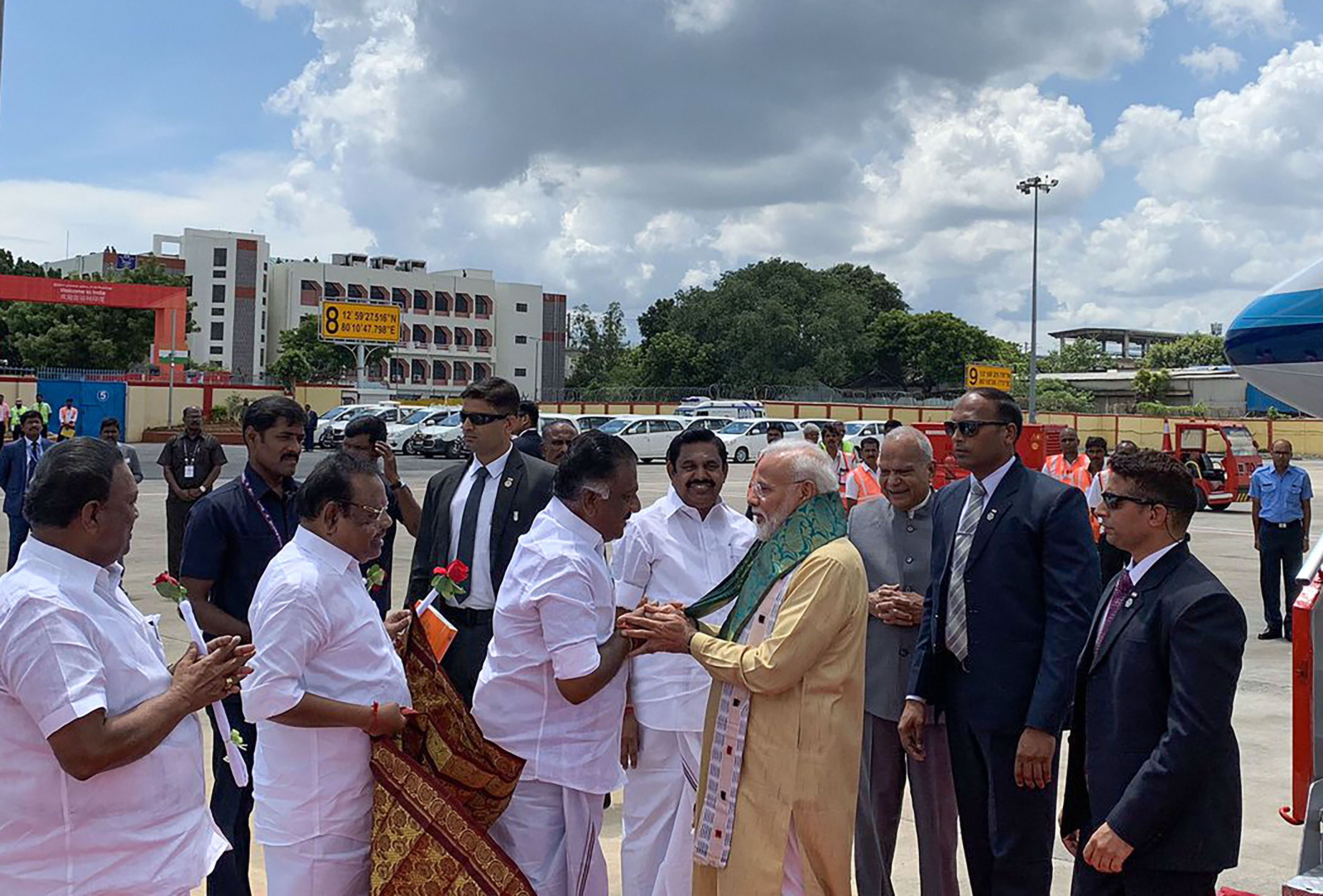 Prime Minister Narendra Modi is welcomed by Tamil Nadu deputy chief minister O. Panneerselvam as chief minister K. Palaniswami looks on, on his arrival in Chennai, Friday, October 11, 2019