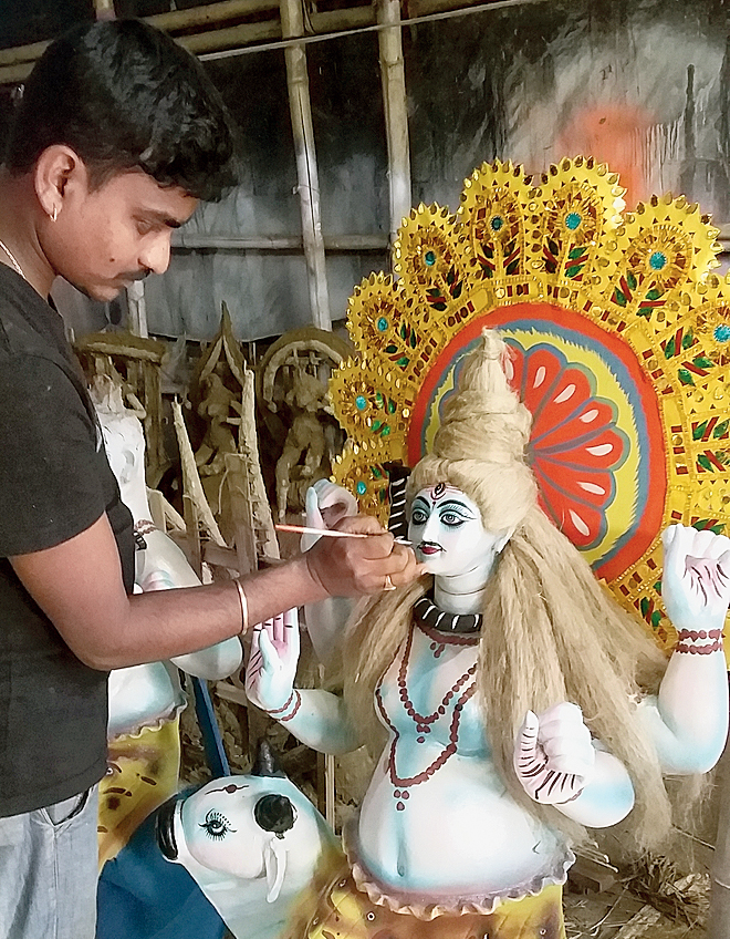 Shankar Pal puts finishing touches to the idol.