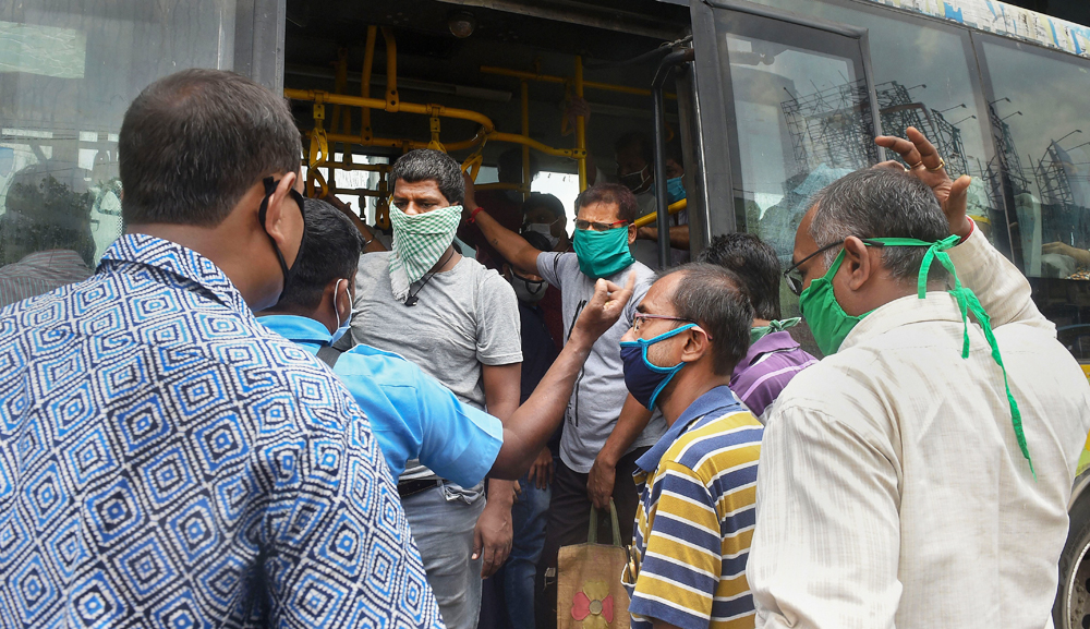 Passengers try to board a bus on the first day of Covid-19 lockdown 5.0, in Calcutta, Monday, June 1, 2020.