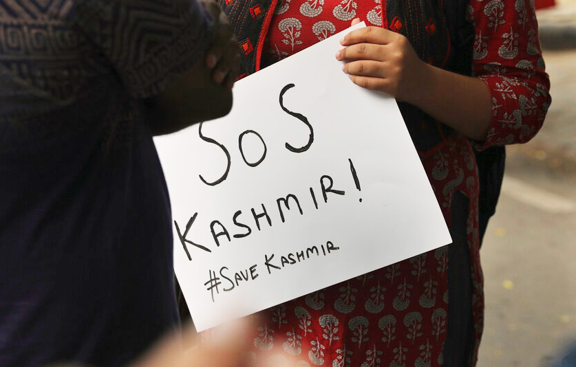 A student holds a banner before a protest against the government revoking Kashmir's special constitutional status in New Delhi, India, Monday, August 5, 2019.