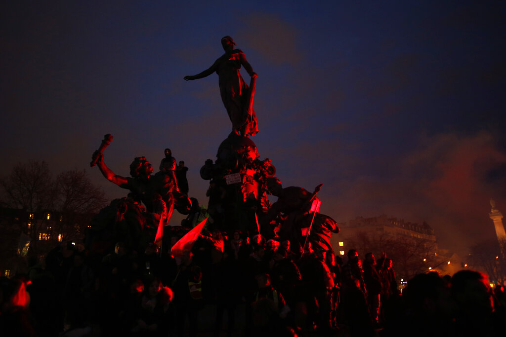 Protestors stand on the statue on the Nation square during a march in Paris, on December 17, 2019