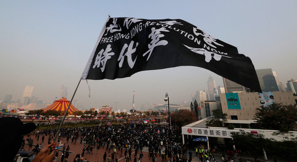 A demonstrator waves a flag as others gather to show support for Uighurs in Hong Kong on December 22, 2019. The flag reads: