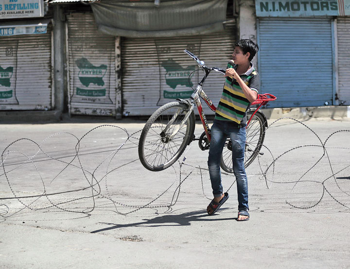 A boy carries his bicycle as he crosses a barbed wire fence in Srinagar on September 9.