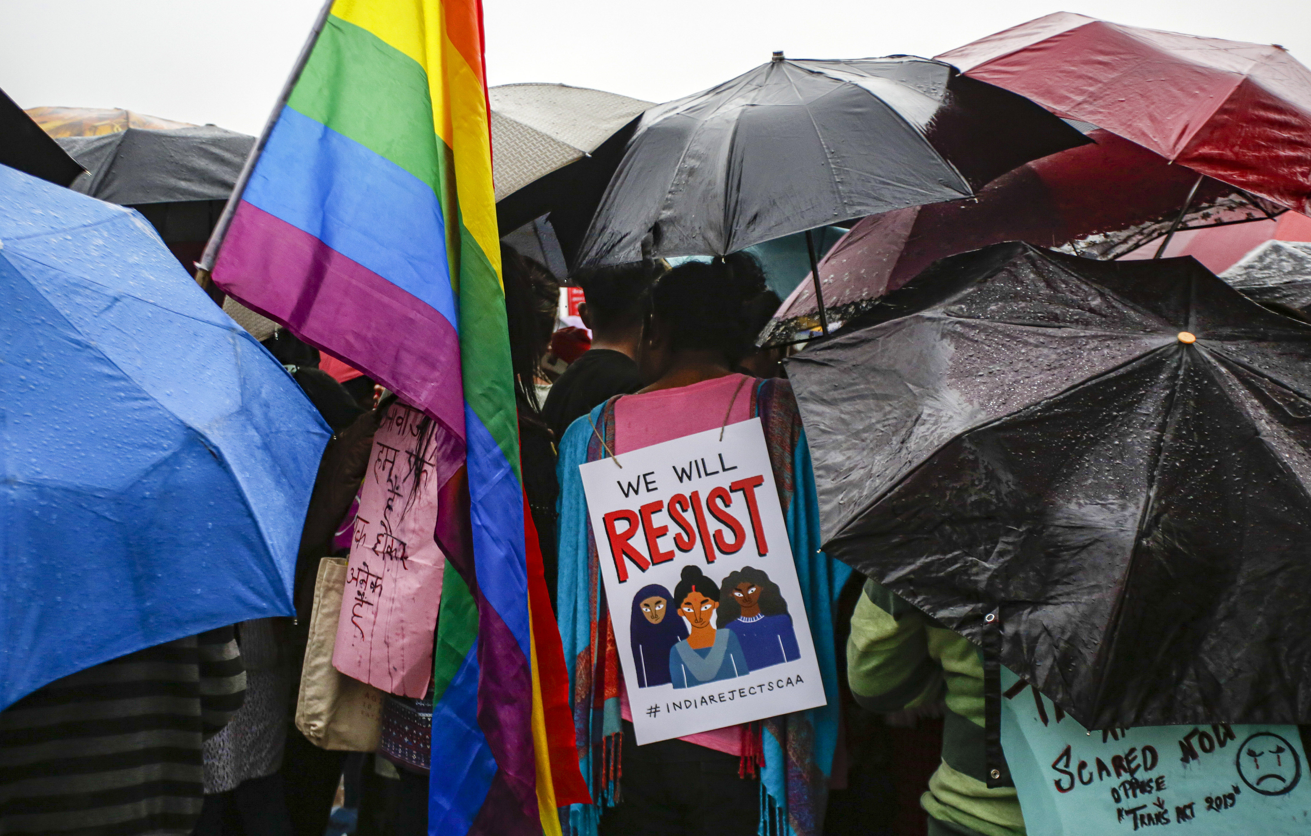 A member of LGBTQ community carries a placard while standing with others holding umbrellas as it rains during a rally to protest against the citizenship law that opponents say threatens India's secular identity, in Kolkata, India, Friday, January 3, 2020