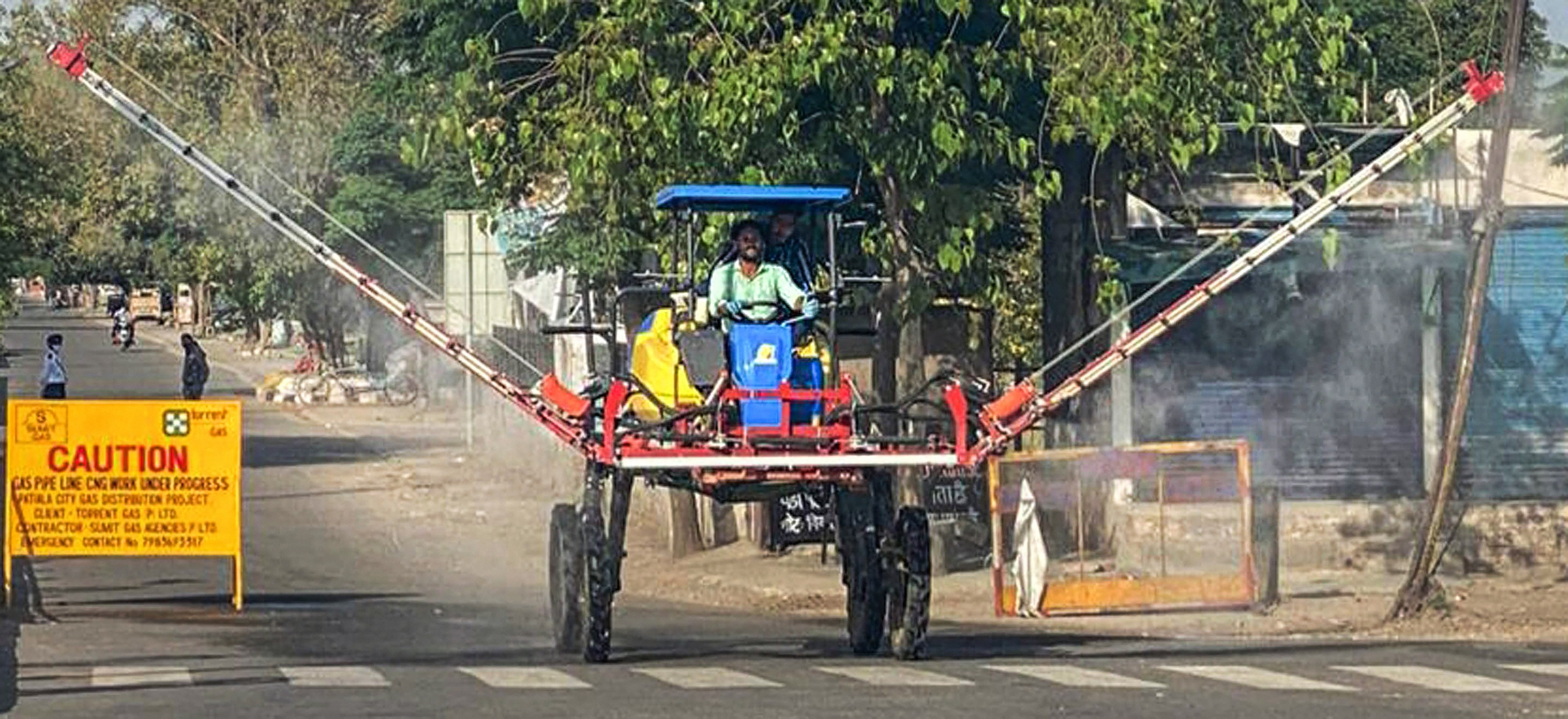 A municipal worker operates a Japanese machine to spray disinfectants on a road, during the nationwide lockdown imposed in wake of the coronavirus pandemic, in Patiala, Friday, April 10, 2020.