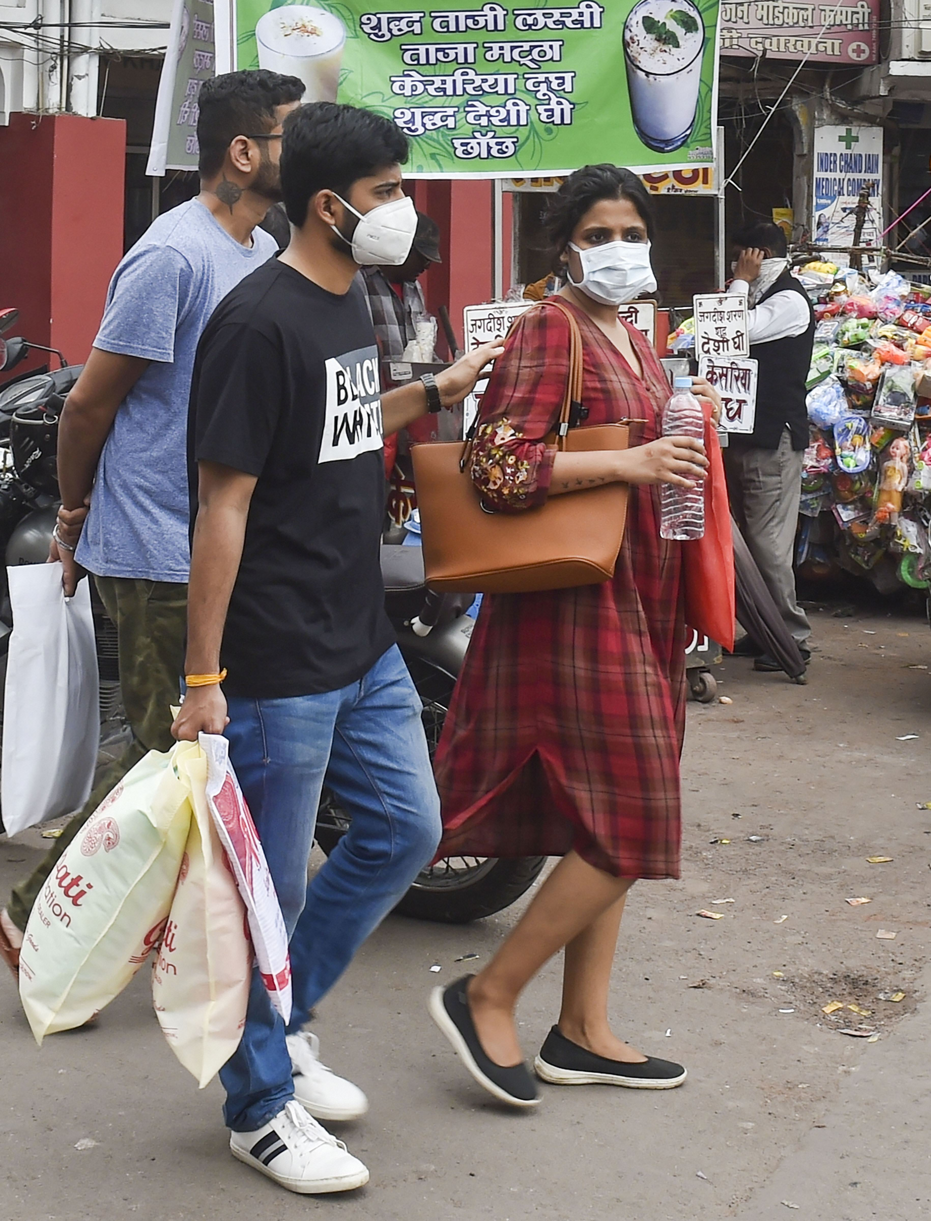 People wear protective masks in view of coronavirus pandemic, at a market in Lucknow on Sunday